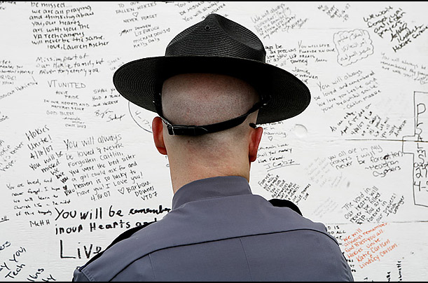 A Virginia State trooper pauses to read messages left for the victims of the shooting