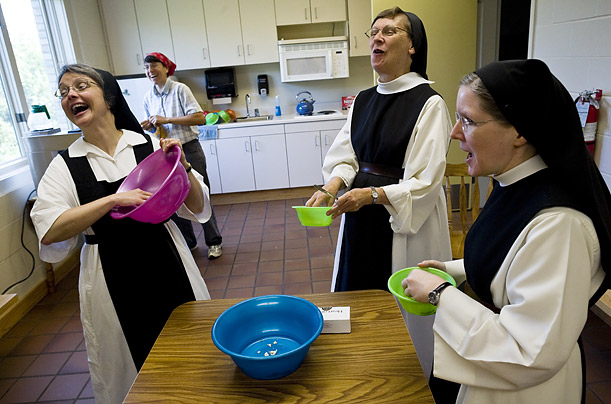 The Trappist nuns of Dubuque, Iowa's Our Lady of the Mississippi Abbey share a light moment while finishing off popcorn in the break room of their candy factory.