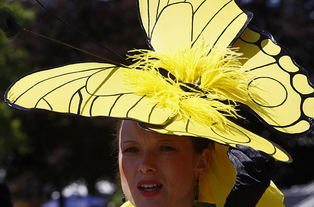 A racegoer finds shade and style under the wings of her butterfly shaped hat