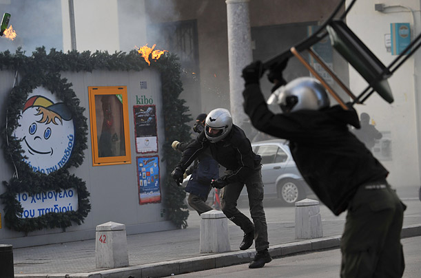 Protesters throw a chair and fire bombs towards riot police during clashes in the northern port city of Thessaloniki
