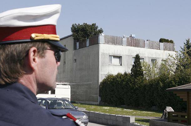 A police officer looks towards the Friztl's house