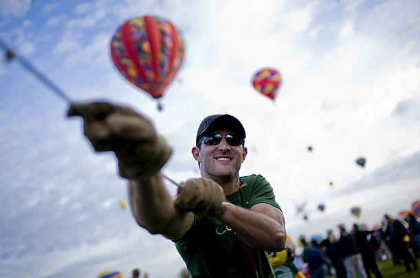 A participants holds on to the crown line of a balloon on the first day of the festival. Albuquerque has a long association with ballooning, going back more than a century.