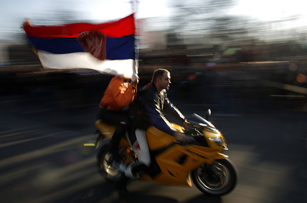 A motorcyclist flies the Serbian flag.