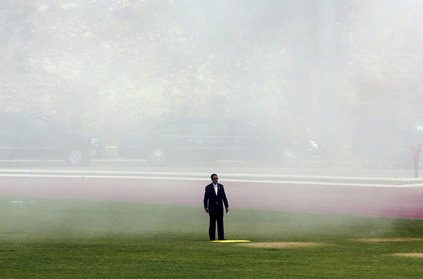 A security officer stands stands in smoke and dust after the helicopter carrying U.S. President George W. Bush, unseen, landed from Tel Aviv in Jerusalem, Wednesday, May 14, 2008.