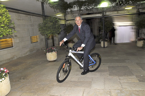 George W. Bush rides a bicycle he received as a gift from Israeli Prime Minister Ehud Olmert, Israel, Thursday, May 15, 2008.