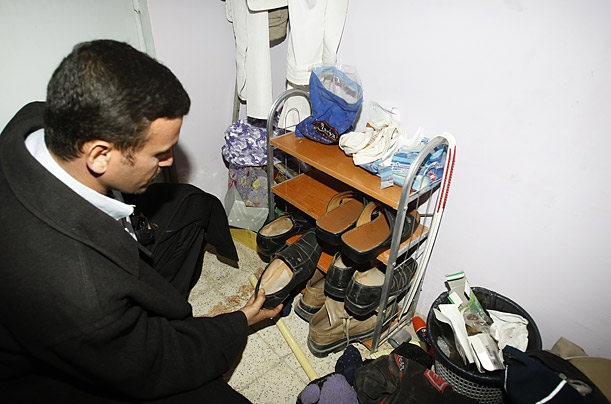 Al-Zaidi's brother Dargham displays his brother's shoe rack at the their home in Central Baghdad.