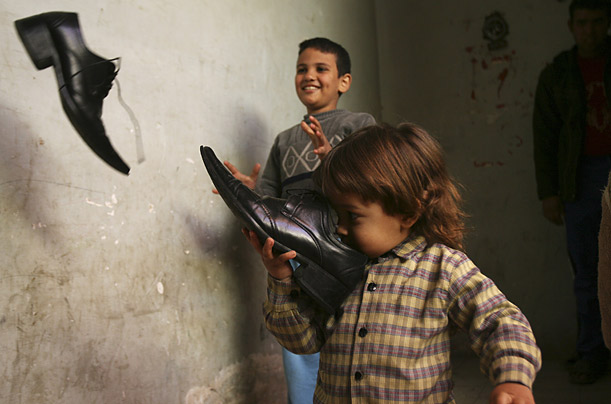 Children in al-Zaidi's building play with another pair of his shoes.