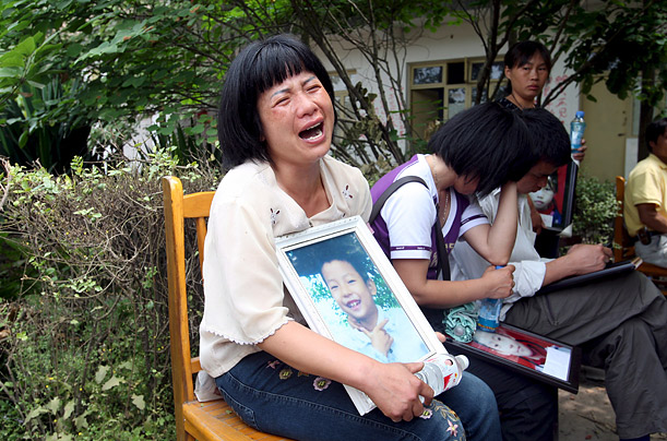A mother wails while holding a framed photograph of her child, one of 127 children killed in the collapse of Fuxing Number Two Elementary School in Mianzhu.