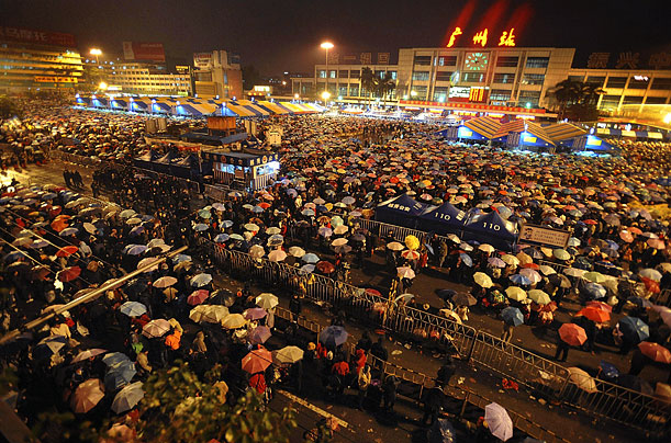 Thousands of passengers wait in the rain outside the railway station in Guangzhou