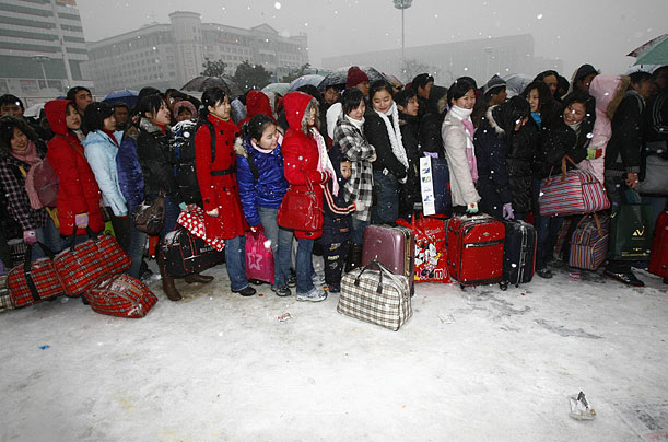 Hopeful passengers wait in line in a snow-covered yard in Wuhan