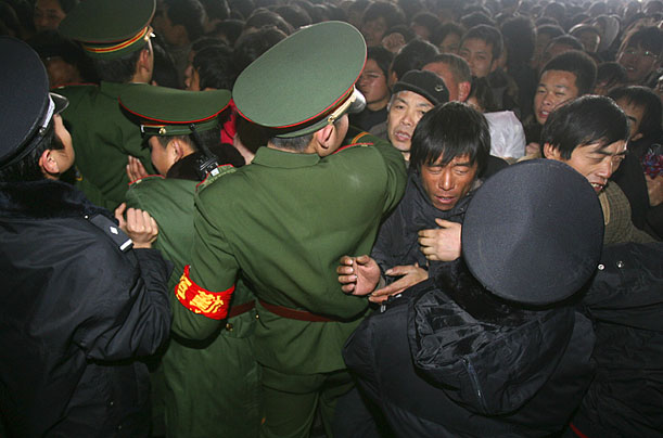 Paramilitary police control a crush of people trying to buy rail tickets in Nanjing