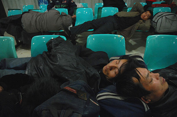 Chinese passengers sleep on benches at the Wuhan railway station