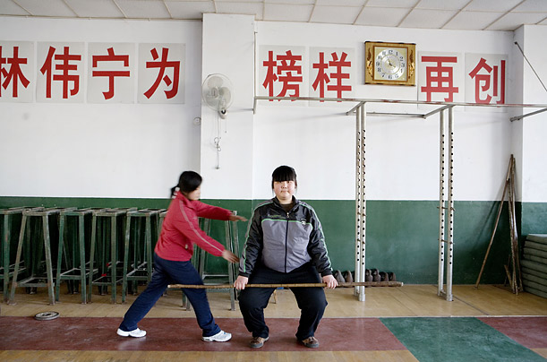 A coach instructs a new student in weight lifting at the Weifang City Sports School, one of 3,000 state-run athletic academies that train nearly 400,000 youngsters.