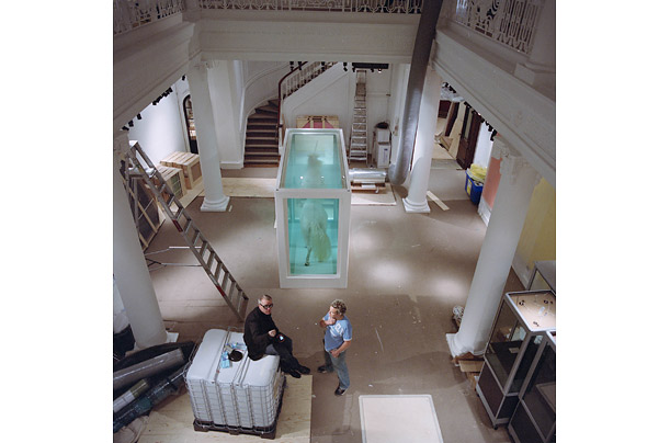 Hirst sits in one of the Sotheby's exhibit spaces. The work in the center of the hall, titled
