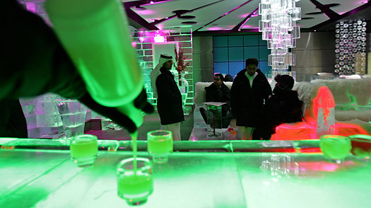 A bartender pours fruit juice for guests at the Chillout ice lounge in Dubai, United Arab Emirates