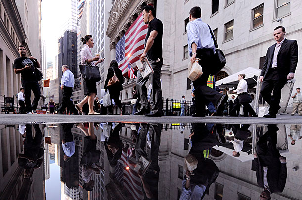 29 Sep 2008, People walk along Wall Street past the New York Stock Exchange at the start of the trading day in New York. Markets around the world are reacting to the United States' government plan to bailout failing banks and financial institutions.