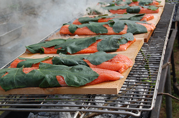 Cedar-planked salmon wrapped in fig leaves simmer on a grill set up table-side at Sauvie Island Organics.
