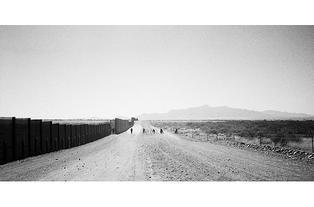 A group of would-be immigrants, believing the photographer and the writer to be members of law enforcement, dash back towards the Mexican side.