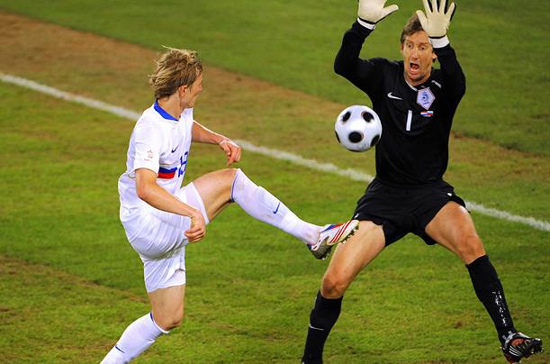 Russian forward Pavluchenko tries to lob Dutch goalkeeper Edwin Van der Sar