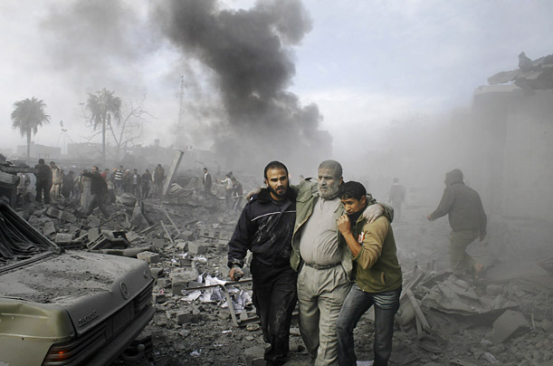 After a direct hit, an injured Palestinian man is helped away from the scene of devastation in Rafah