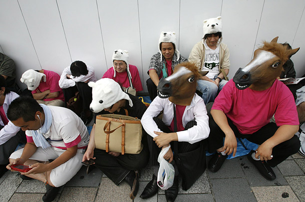 Customers wearing animal masks wait in line to purchase the iPhone 3G near the Softbank Corp flagship store in Tokyo's Omotesando shopping district July 11, 2008.
