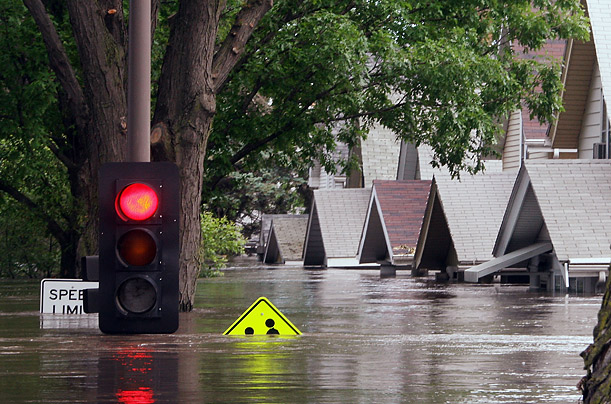 In Cedar Rapids, the rain-soaked Cedar River inundates a local street. Nine of the rivers in the state have risen to record levels.