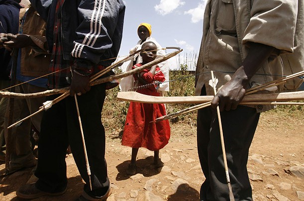 A Kikuyu girl stands between two warriors armed with bows and arrows. Though political rivals Mwai Kibaki and Raila Odinga have established an uneasy truce, the violence inspired