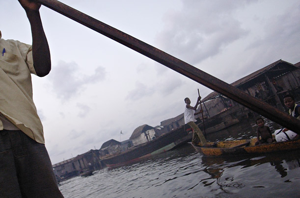 Impoverished Nigerians use poles to push their boats through the canals of the Lagos slum Ilage.