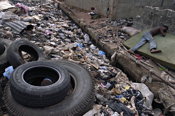 A poverty-stricken boy sleeps next to a canal filled with garbage in the Lagos slum Ilage.
