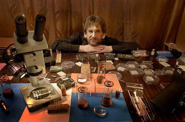 The artist poses with the tools of his trade in his Moscow apartment. His tools include superglue, syringes and toothpicks. The microscope dates to 1985.