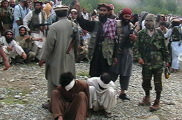 Taliban militants prepare to kill two men suspected of cooperating with the U.S.