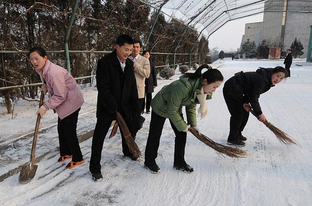 North Korean hotel staff clear snow from the road before the departure of the New York Philharmonic orchestra for rehearsals in Pyongyang on February 26, 2008.  Th