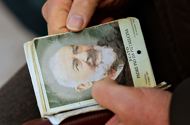 A pilgrims holds an mass booklet before an open mass to mark the anniversary of Padre Pio's death and the display of his body