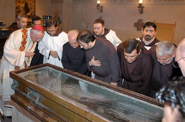 Archbishop Domenico D'Ambrosio, left, and other priests look at the coffin containing the remains of Padre Pio