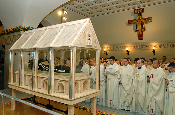 Prelates view and photograph the body of Padre Pio, an Italian saint, laying in repose inside a crystal casket in the crypt of the church of Santa Maria delle Grazie in San Giovanni Rotondo, Italy