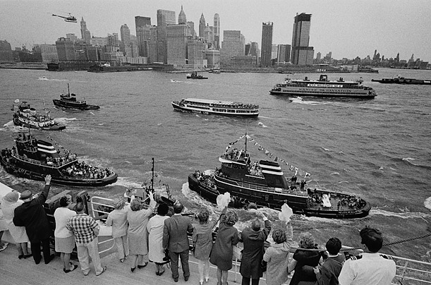 Passengers aboard the ship wave to tugboats and excursion boats as they enter New York harbor during the liner's maiden voyage from Southampton, England, to New York City.