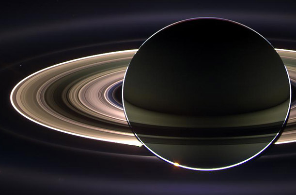 In this composite photograph compiled from images produce by the Cassini craft in 2006, the Earth appears as a tiny pinprick of light between Saturn's outer rings.