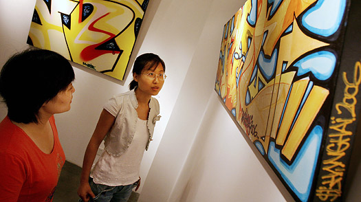Two Chinese art students look at graffiti art on a canvas by French graffiti artist Nebay, that is on display at the Moganshan art complex in Shanghai China