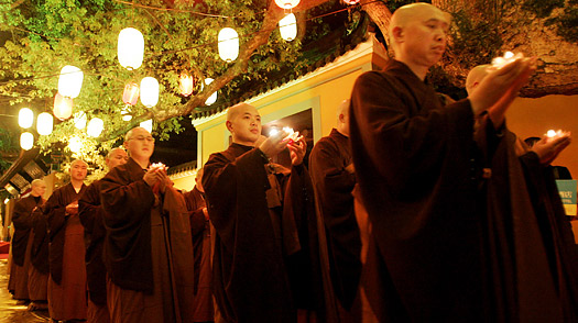 Buddhist monks walk with candles during