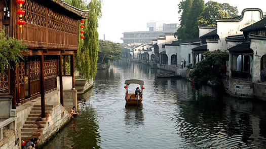 A boat sails past civilian houses along a river in Nanxun town in Huzhou city, east China
