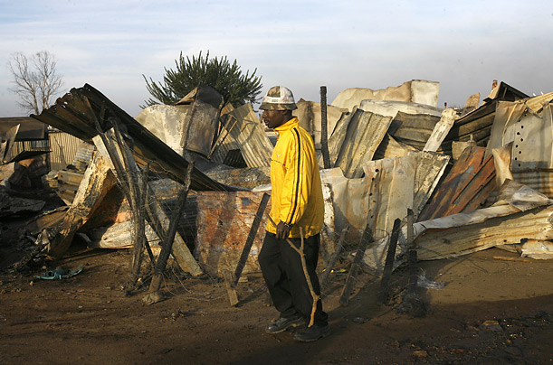 A man walks past shacks destroyed during riots in the Reiger Park informal settlement outside Johannesburg Monday May 19, 2008.
