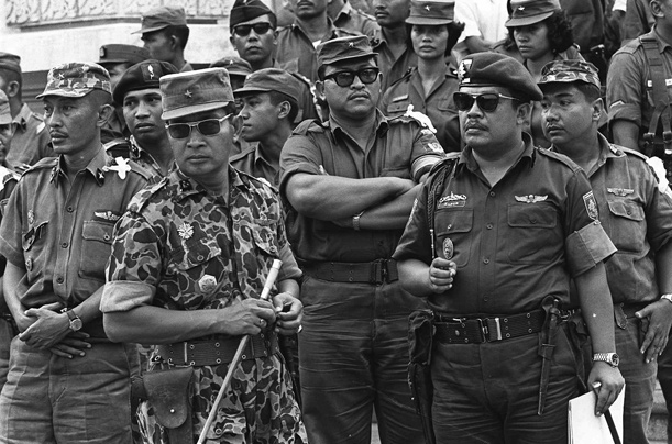 General Suharto was able to in 1965 successfully suppress a group of junior army officers who attempted a coup. he then seized power for himself and began a bloodbath in which close to 1 million Indonesians were killed. These Indonesians were killed under suspicion of their affiliation with other communist nations.