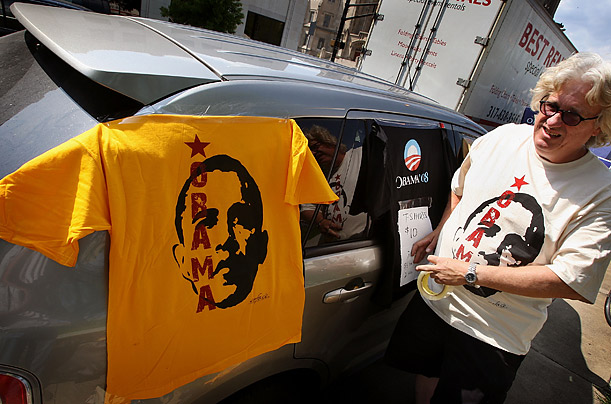 An Obama supporter sells shirts at buttons at a rally.