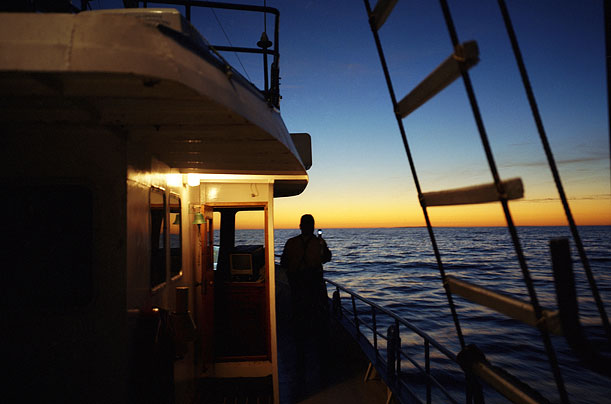 A tuna fisherman photographs the sunrise