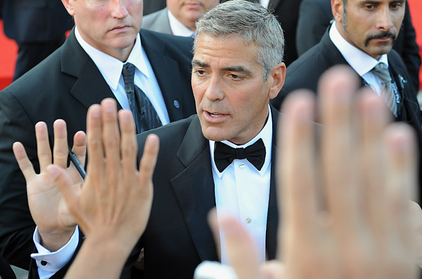 US actor George Clooney signs autographs as he arrives for the screening of the movie