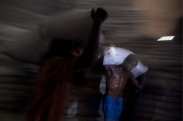 A porter carries a bag of sorghum wheat through the WFP's giant warehouse in Kampala