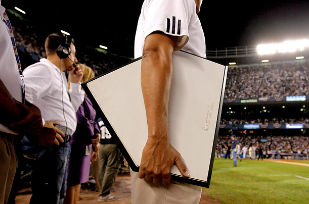 A member of the stadium grounds crew holds the home plate to be used in the final game, played against the Baltimore Orioles.