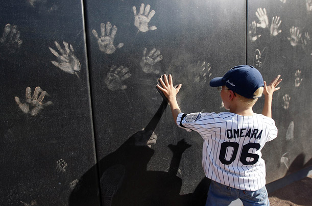 A boy leaves handprints on the outfield wall. Fans were allowed to walk the track around the field before the game.