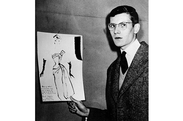 Yves Saint Laurent holds up a drawing of his cocktail dress design that won him first prize in 1953 in a fashion drawing competition, sponsored by the International Wool Secratariat, in Paris.