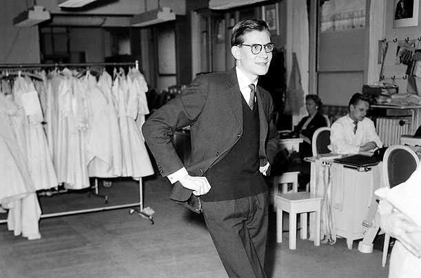 March 14, 1958. Yves Saint Laurent stands on one leg, his favorite position, as he studies a new design in his atelier in Paris, France.  When Dior died suddenly in 1957, Saint Laurent was named head of the House of Dior at the age of 21.